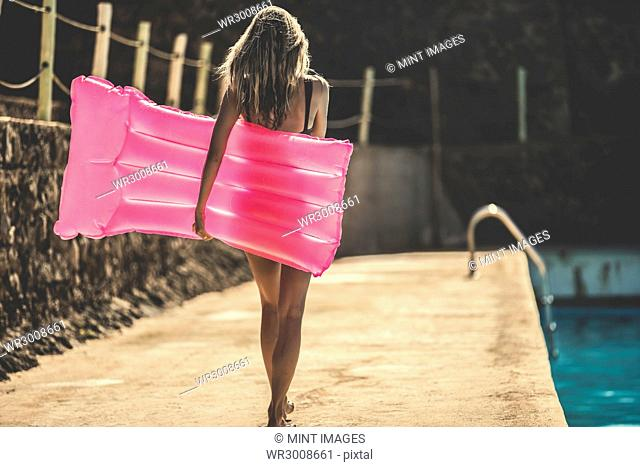 Rear view of a young woman wearing a swimsuit carrying a pool raft next to a swimming pool