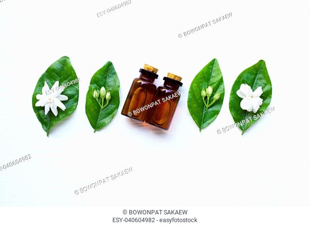 Essential oil with jasmine flower on white background