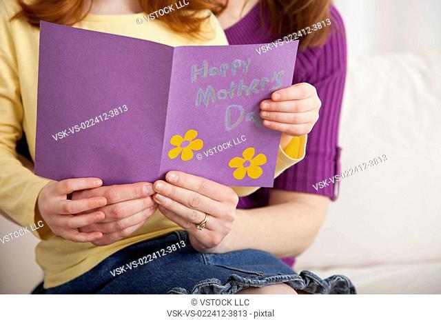 USA, Illinois, Metamora, Close up of daughter (4-5) and mother holding greeting card for Mother's day