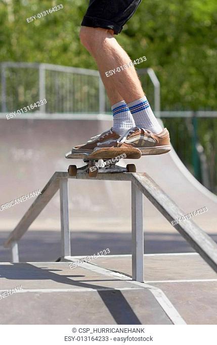 Skater doing 50-50 grind on fun-box in skatepark