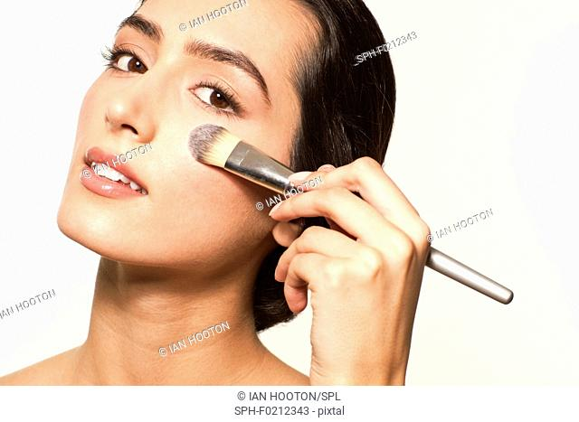 Woman applying foundation with brush