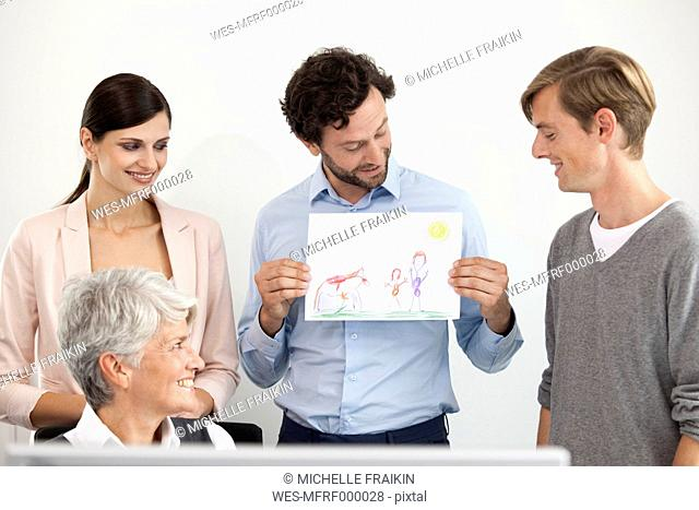 Businessman showing child's drawing to colleagues