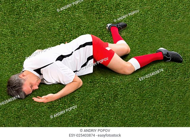 Male Soccer Player Suffering From Injury Lying On Grass