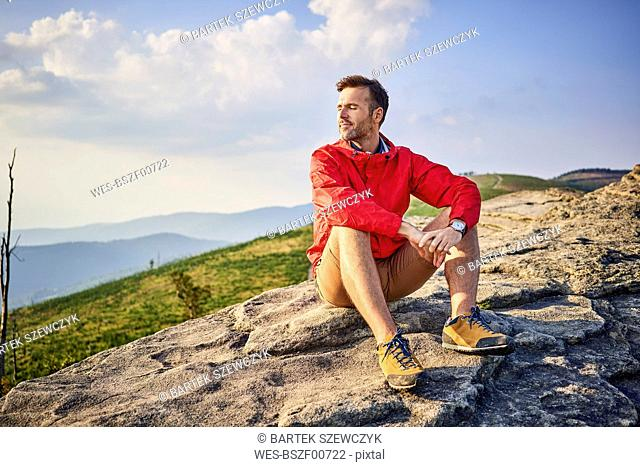 Man sitting on rock enjoying serene moments during hiking trip
