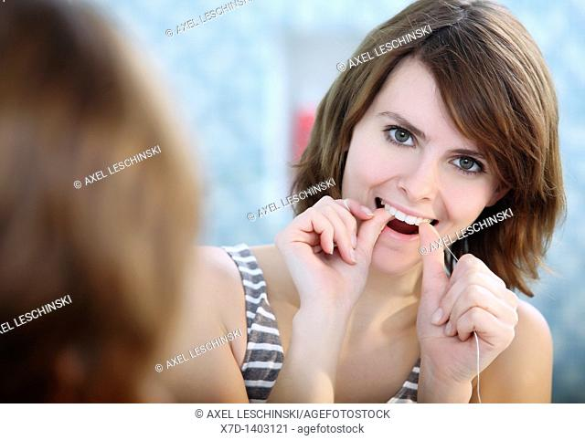 woman cleaning her teeth with dental floss