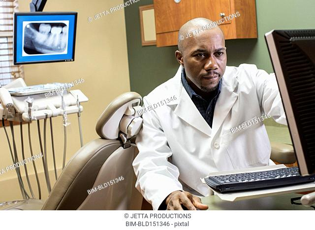 Black dentist using computer in office