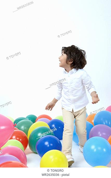 Side view of smiling boy playing in colorful balloons