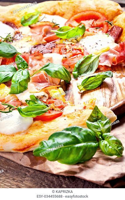 Pizza with prosciutto, mozzarella, tomatoes and basil, selective focus