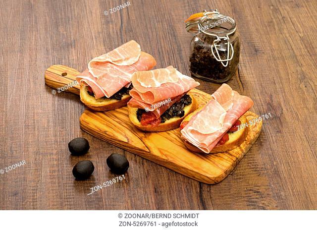 Crostini mit schwarzer Tapenade und rohem Schinken auf einem Brett aus Holz