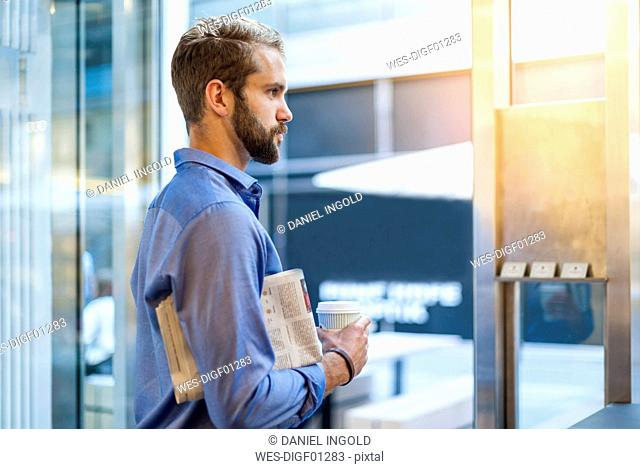 Young man with newspaper and takeaway coffee looking out of window
