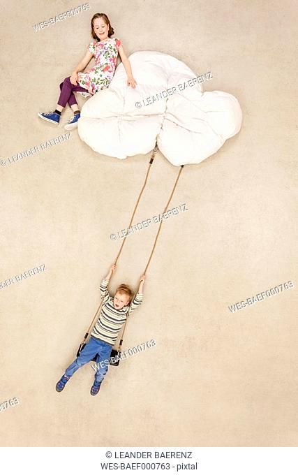 Children swinging on clouds