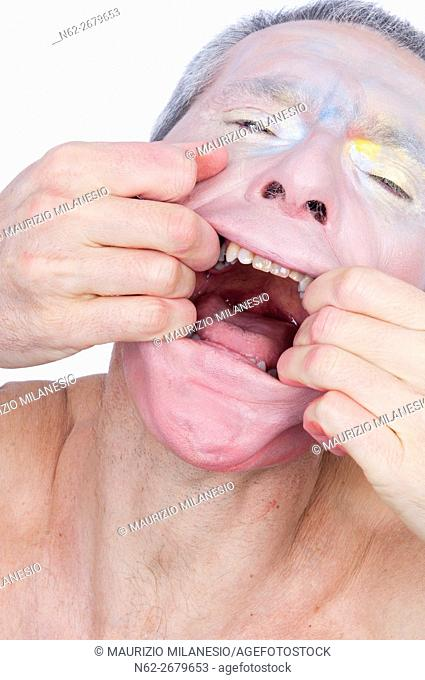 Portrait of a crazy clown with smeared makeup on his face, he splays his mouth with his hands vigorously