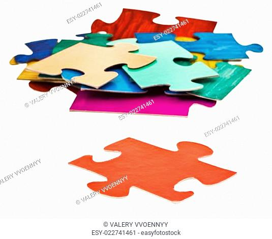 separate piece in front of pile of jigsaw puzzles