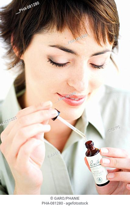 Woman using a Bach rescue remedy liquid flower extract to reduce stress and anguish