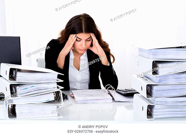 Young Depressed Businesswoman Checking Invoice In Office