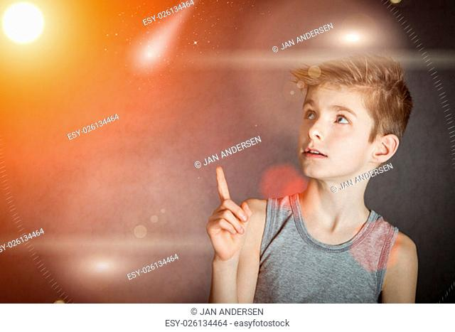 Close up Curious Young Boy Pointing his Finger Up to Glowing Lights Against Abstract Background