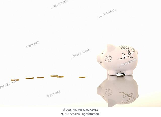 piggy bank object with coins on reflective surface