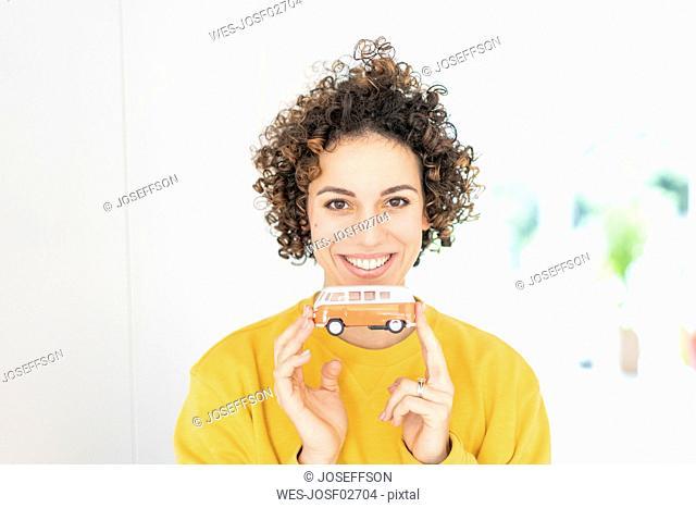 Portrait of smiling woman holding camper van model