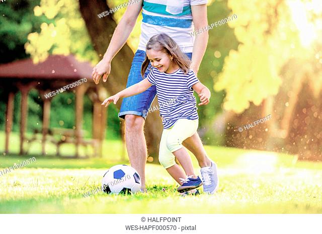 Happy little girl playing soccer with her father in a park