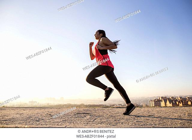 Young woman running on path