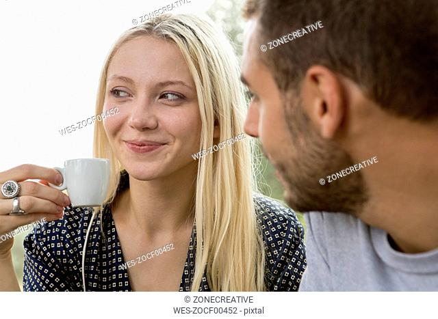 Portrait of smiling blond woman with espresso cup watched by her friend