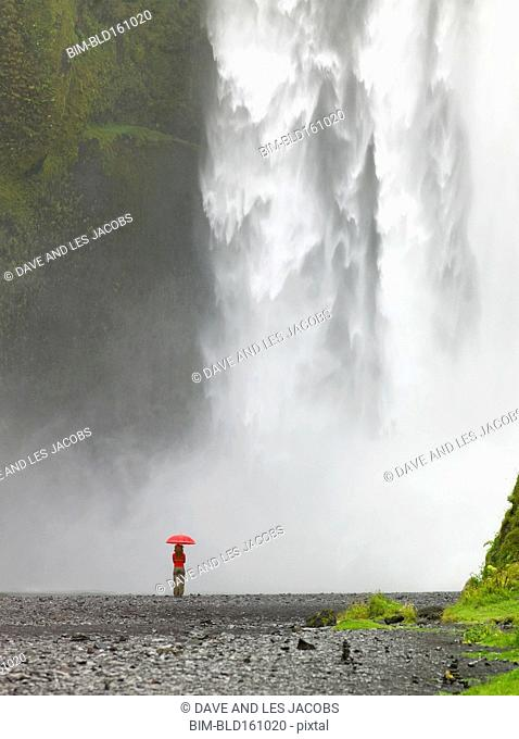 Caucasian woman holding umbrella admiring waterfall