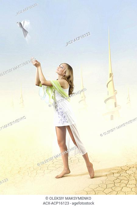 Digital photo-illustration of a Young beautiful girl in a fantastic extraterrestrial desert world covered with sand and dust and high spiral towers in the...