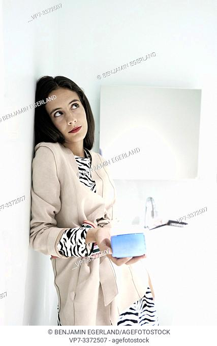 woman holding cosmetic product