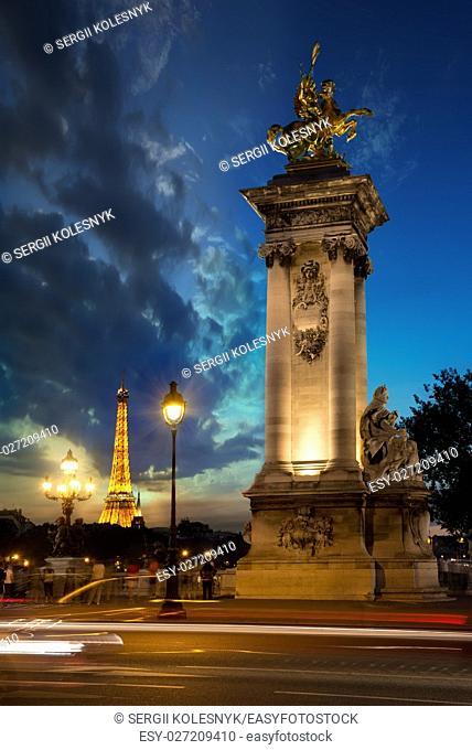 PARIS, FRANCE - AUGUST 25, 2016 : Column on bridge Alexandre III and Eiffel Tower at sunset in Paris, France