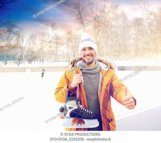 happy young man showing thumbs up on skating rink