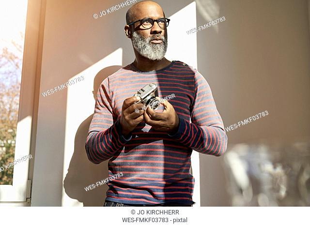 Mature man holding vintage camera