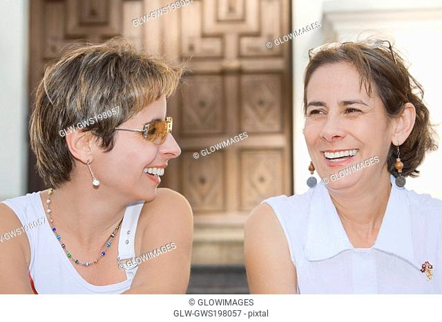 Close-up of a mid adult woman sitting with a mature woman and laughing