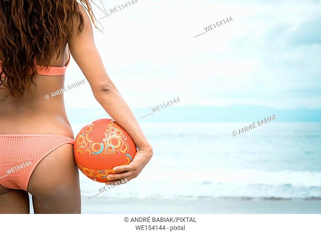 Woman beach fitness - back side of attractive female holding beach volleyball, Riviera Nayarit, Mexico