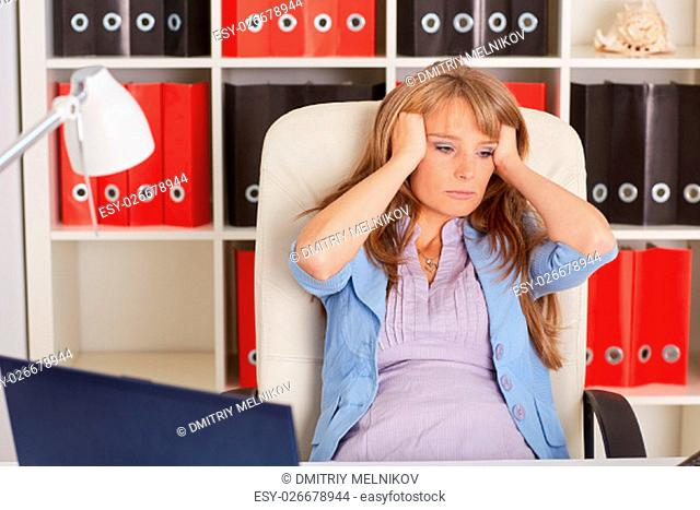 Tired unhappy business woman sits on an armchair in the office