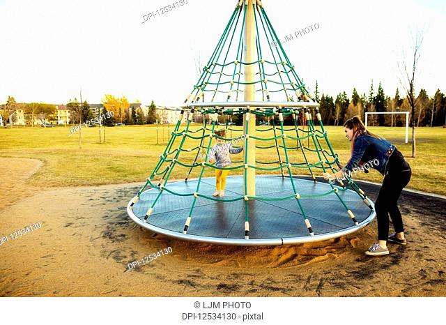 A young mom spinning her daughter while playing on a merry go round with a rope climber in a playground at sunset during a warm autumn evening; Edmonton