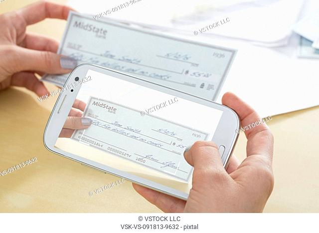 Teenage girl (14-15) photographing cheque with cell phone