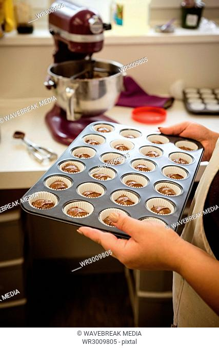 Woman holding baking tray with cupcakes
