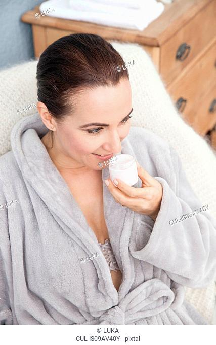 Woman relaxing at home, smelling moisturiser