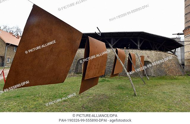 26 March 2019, Brandenburg, Glindow: In front of the disused ring kiln of the brick factory, metal sheets hang on a leash; the artist Chris Heinze called his...