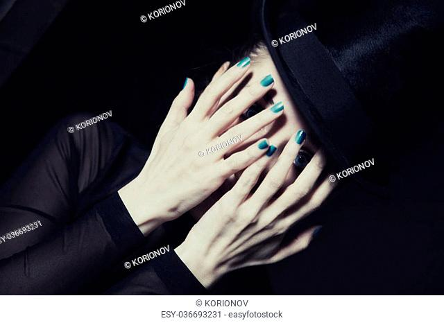 Portrait of beautiful young woman covering face with her hands