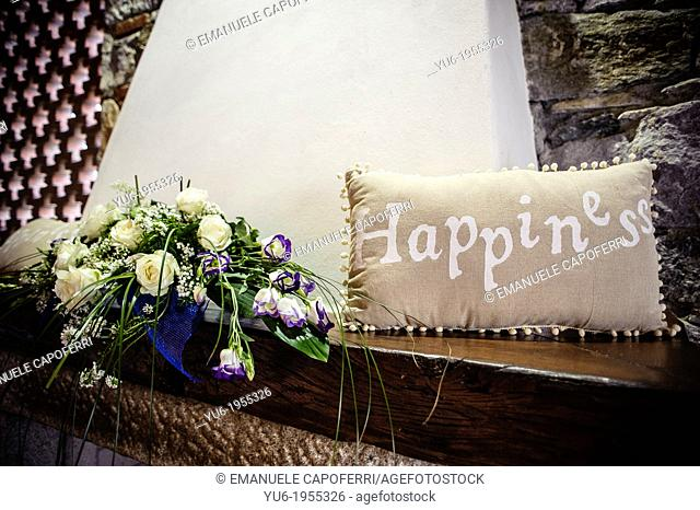 Flowers and cushion with happiness written