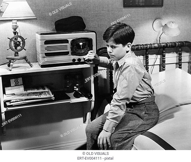 Boy listening to radio in bedroom All persons depicted are not longer living and no estate exists Supplier warranties that there will be no model release issues