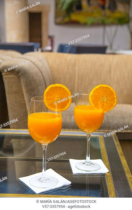 Two glasses of orange juice in a dining room