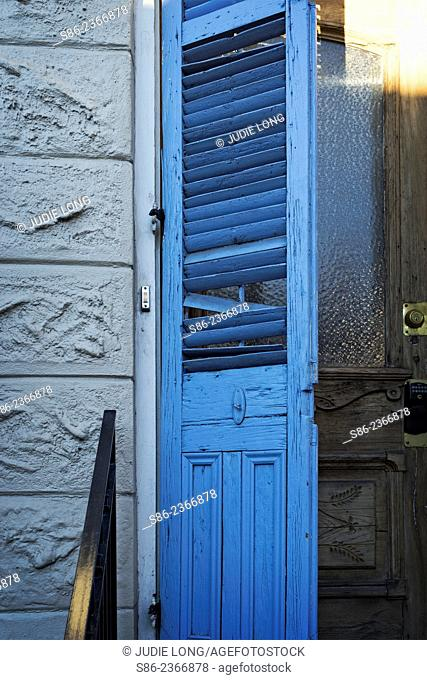 Blue Shutter Door with broken louvers. semi open, on a front entry door of a building in the French Quarter of New Orleans, Louisiana, USA