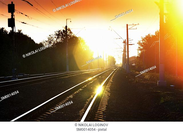 Sunset railway with light leak landscape background