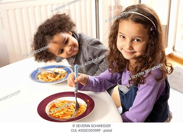 Girls eating pasta together at table