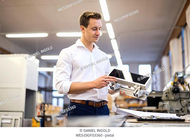 Smiling young businessman in factory holding component