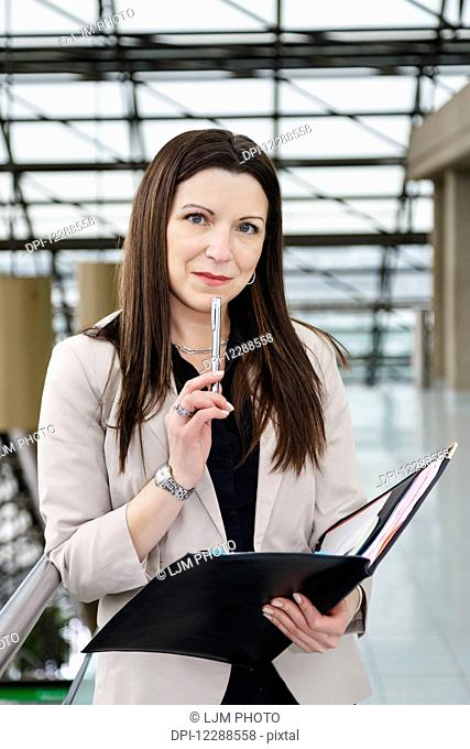 Portrait of a mature business woman holding a portfolio in the atrium of an office building; Edmonton, Alberta, Canada