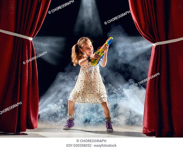 Cute little child girl playing guitar on stage. Kid dreams of becoming a rock musician
