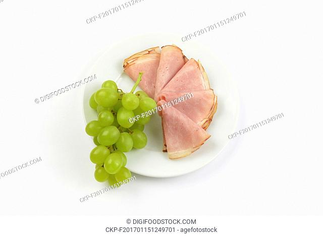 plate of ham slices with bunch of white grapes